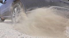 Car starts and quickly drives away, tires raising sand and dust on gravel road Stock Footage