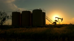 Industrial jack pump platform pumping crude oil against sunset sun - stock footage