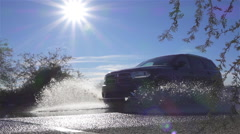 SLOW MOTION: SUV car diving over big water puddle, splashing water into camera Stock Footage