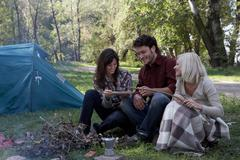 Three people at campsite cooking hot dog Stock Photos