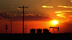 Oil pump jack containers and electrical wiring at amazing sunset Stock Footage