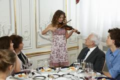 Girl playing violin to family - stock photo