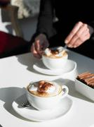 Cappuccino on table woman stirring cup Stock Photos