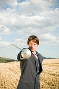 Businessman fencing in wheat field. - stock photo
