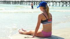 Beautiful college girl sitting at beach near water Stock Footage