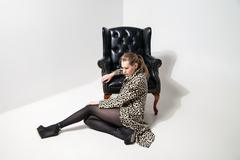 Girl in leopard print coat near armchair Stock Photos