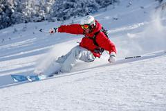 Man smiling skiing down slope Stock Photos