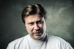 emotional angry middle aged man over gray - stock photo