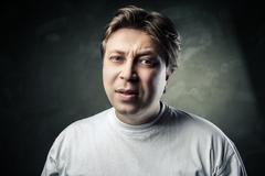 emotional middle aged doubting man over gray - stock photo