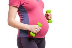 Happy pregnant mom exercising with dumbbells Kuvituskuvat