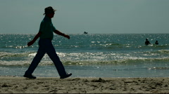 Silhouette man walking on beach shore line Stock Footage