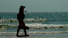 Silhouette woman walking along shore line at beach - stock footage