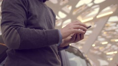 Man using the smartphone while charging its electric car Stock Footage