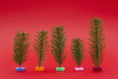 Variety of small Christmas trees on red background Stock Photos