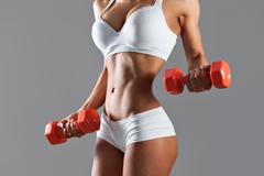 Sexy woman doing exersise with dumbells - stock photo