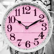 Pink clock in a classical style. Stock Photos