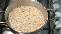 Cooking pearl-barley porridge on the gas stove Stock Footage