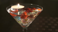 Candle burns in a glass with scattered gemstones Stock Footage