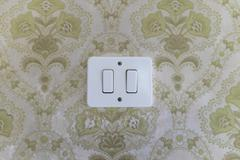Light switch on patterned wall Stock Photos