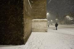 City building and pedestrian in snow storm at night Stock Photos