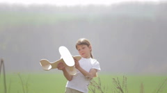 Portrait of a child with a wooden plane in a field. Stock Footage