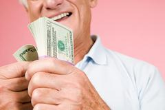 Man with bundle of banknotes - stock photo