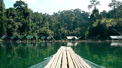 Thailand. Khao Sok National Park. Sail Raft on lake moving among camping. - stock footage