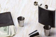 Metal flask trimmed leather, three metallic  shot glasses and wallet. - stock photo