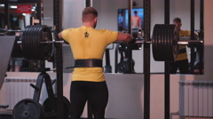 The man squats with a barbell Stock Footage
