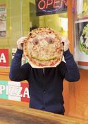 Man holding pizza with anthropomorphic face - stock photo