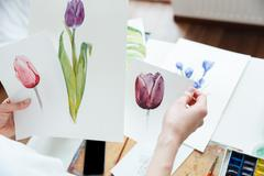 Woman painter holding pisctures of flowers in art studio Stock Photos