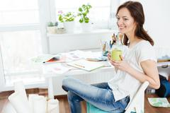 Relaxed happy woman artist drinking coffee in workshop - stock photo