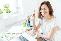 Happy pretty woman artist using laptop in art studio Stock Photos