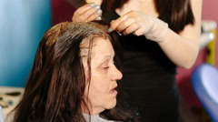 Hairdresser dye the hair of the old woman - stock footage