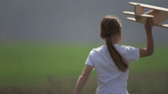 Portrait of a child with a wooden plane in a field. - stock footage