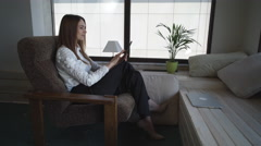 Happy businesswoman sitting on the armchair with a tablet has a break - stock footage
