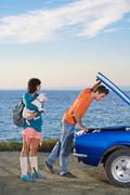 Man and woman man looking under bonnet - stock photo