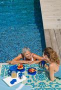 Woman in swimming pool talking to woman Stock Photos