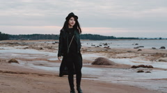 Girl in a black dress walking along the rocky shore of the gulf Stock Footage