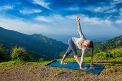 Woman doing Ashtanga Vinyasa yoga asana Parivrtta trikonasana - stock photo