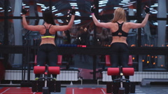 Two girls do a hyperextension in the gym Stock Footage