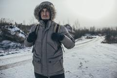 Thoughtful hiker carrying backpack while standing on snow covered landscape Stock Photos