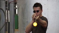 Craftsman working with molten glass in Moser glass factory Stock Footage