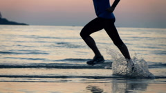 Jogger legs running on the beach during sunse, super slow motion, shot at 240fps Stock Footage