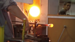 Glass craftsman working with molten glass at Moser glass factory Stock Footage