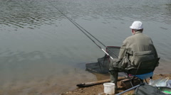 Old fisherman casting rods on the lake, fishing by Pakito. Stock Footage