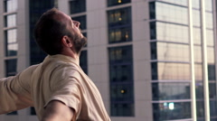 Young man in bathrobe stretching his arms on terrace in the city Stock Footage
