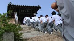 Pilgrims move upstairs approaching Haeinsa Buddhist temple in Haeinsa, Korea. Stock Footage