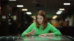The beautiful woman is waiting for the order working with the cellphone in her Stock Footage