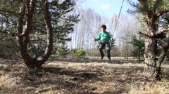Gomel, Belarus - April 3, 2016: Family in a forest glade ride on a swing. Stock Footage